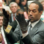 O.J. Simpson looks at a new pair of Aris extra-large gloves that prosecutors had him put on 21 June 1995 during his double-murder trial in Los Angeles.