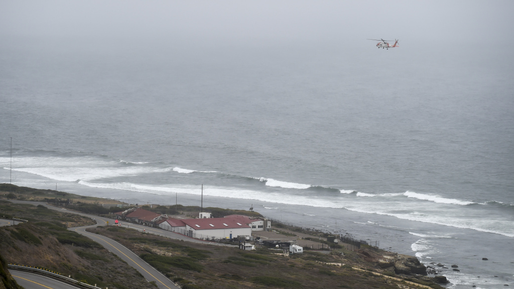 A U.S. Coast Guard helicopter flies over the area where a boat capsized just off the San Diego coast Sunday.