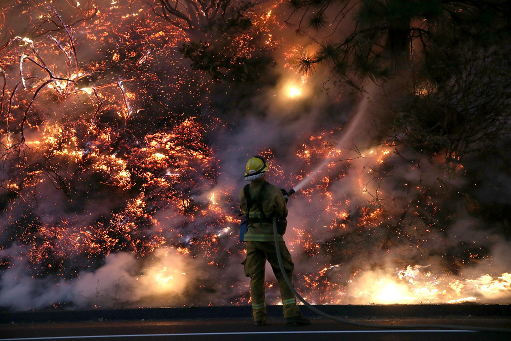 A firefighter uses a hose to douse the flames of the Rim Fire on Saturday, Aug. 31, 2013 near Groveland, California.