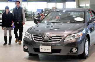 Customers check a Toyota Camry at the company's showroom in Tokyo on January 27, 2010.