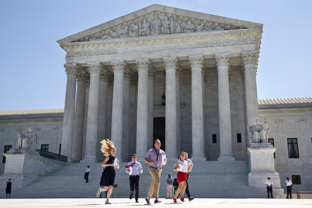 New interns run with a decision across the plaza of the Supreme Court in Washington, Monday June 29, 2015. On Monday, the court upheld Arizona congressional districts drawn by an independent commission in a ruling that preserves efforts in 13 states, California included, to limit partisan influence in redistricting.