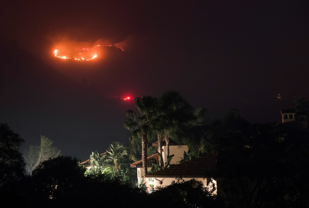 Fire burns in the hills behind a home at the Thomas Fire, December 16, 2017 in Montecito, California.