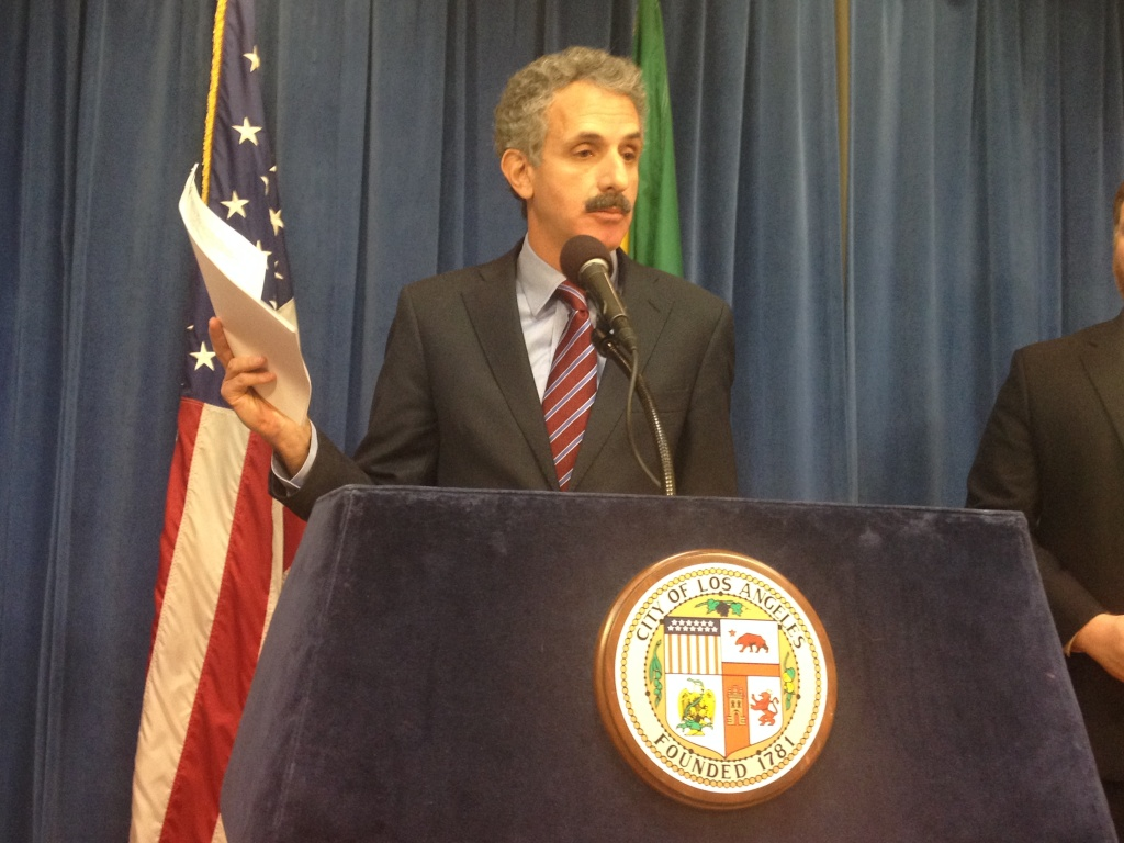 In this file photo, L.A. City Attorney Mike Feuer holds a complaint against Time Warner Cable during a press conference Friday, March 14, 2014. The city held that Time Warner holds a virtual monopoly on cable TV service in L.A. and has made billions while refusing to pay at least $10 million in various fees. In a settlement reached Tuesday, the company agreed to pay the city $5 million and drop its countersuit.