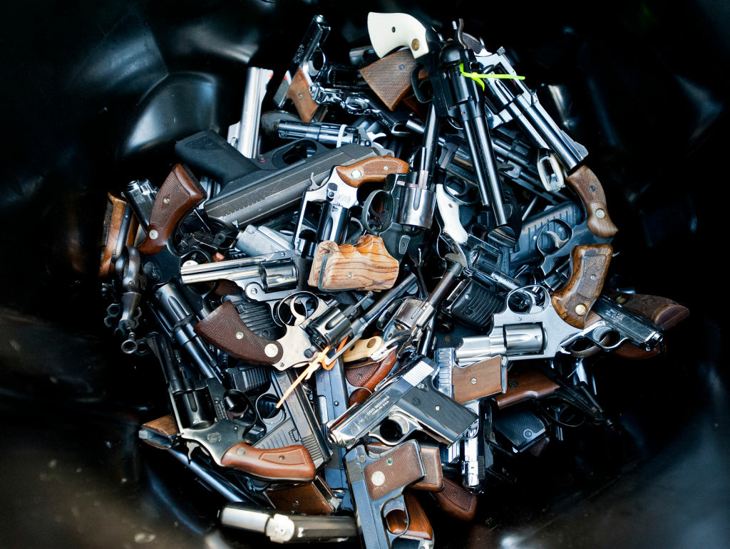 Handguns are thrown into trash bins for melting at a gun buyback event.