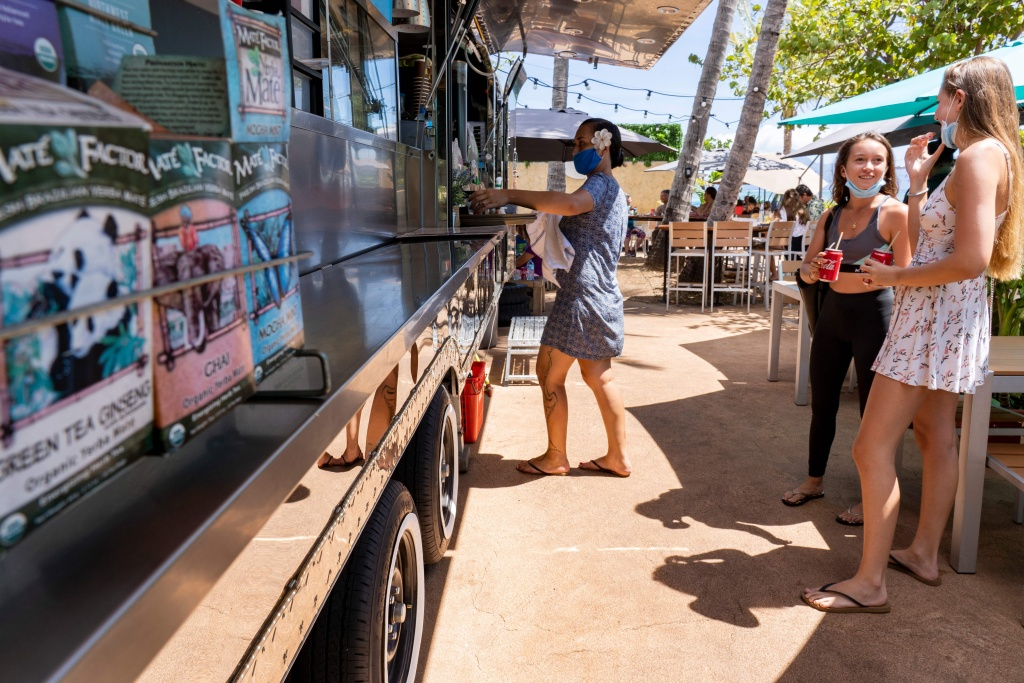 Customers stand in front of a foodtruck in Vaipoopoo Park in Punaauia, south of Papeete on August 25, 2020 amid the Covid-19 (novel coronavirus) pandemic.