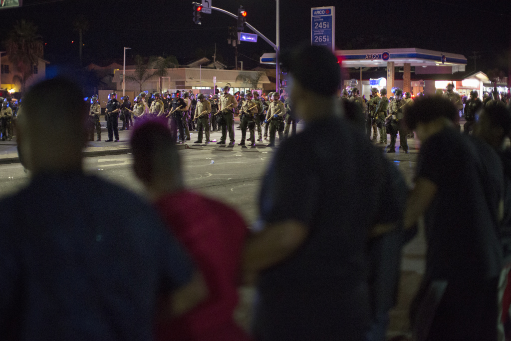 Protesters lock arms as officers amass after an unlawful assembly is declared near the site where an unarmed black man, Alfred Olango, 38, had been shot by police earlier this week on September 29, 2016 in El Cajon, California.