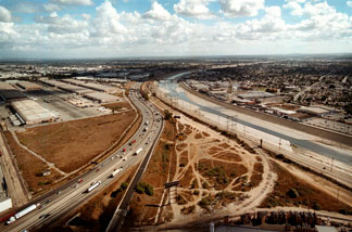 File photo: The cement-confined Los Angeles River, right, slides past open industrial lots in the Los Angeles, CA community of Maywood, November, 2000.