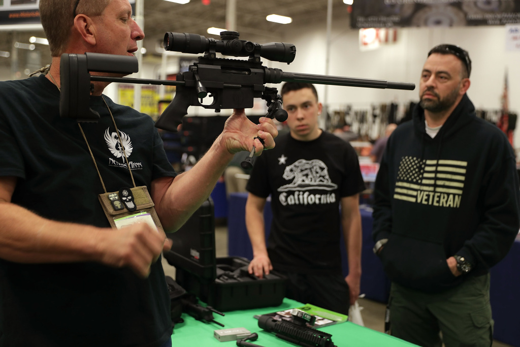 A gun seller demonstrates a firearm to potential buyers during the Nation's Gun Show on November 18, 2016 at Dulles Expo Center in Chantilly, Virginia.