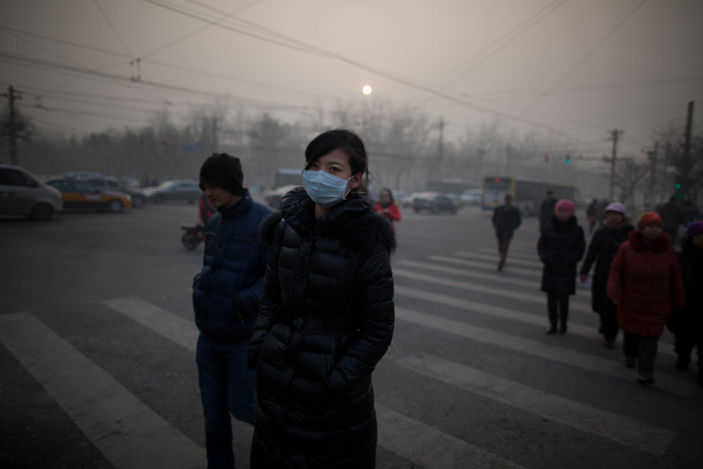 A woman wearing a mask crosses a road during severe pollution in Beijing on January 12, 2013. Air quality data released via the US embassy Twitter feed recorded air quality index levels so hazardous that they were classed as 'Beyond Index'. The US embassy website advised against all outdoor activity.