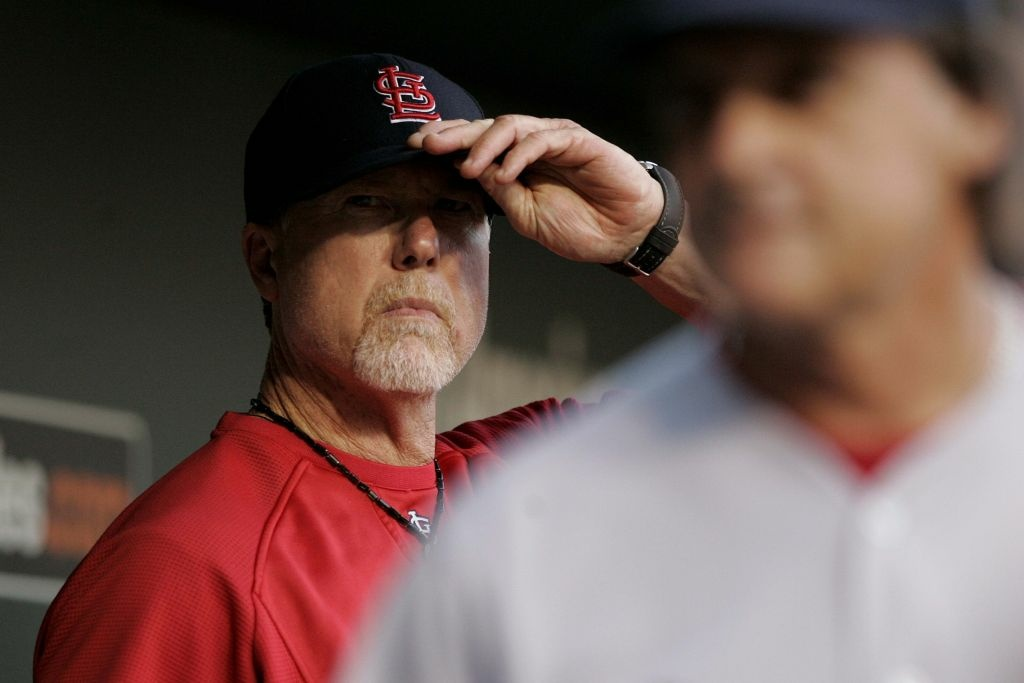 St. Louis Cardinals batting coach Mark McGwire adjusts his cap in the dugout during the start of an interleague basebaseball game at Oriole Park at Camden Yards Thursday, June 30, 2011.
