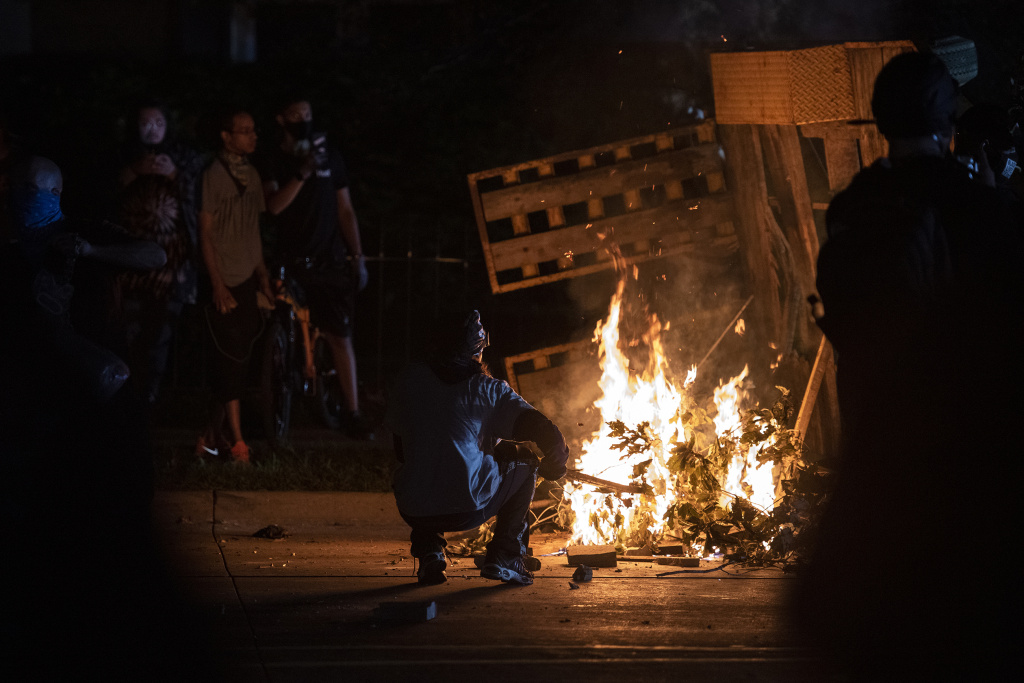 A protester in Kenosha lights some debris on fire on Aug. 26, 2020.