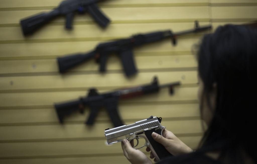 A woman handles a pistol at a gun shop.