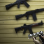 A woman handles a pistol at a gun shop.