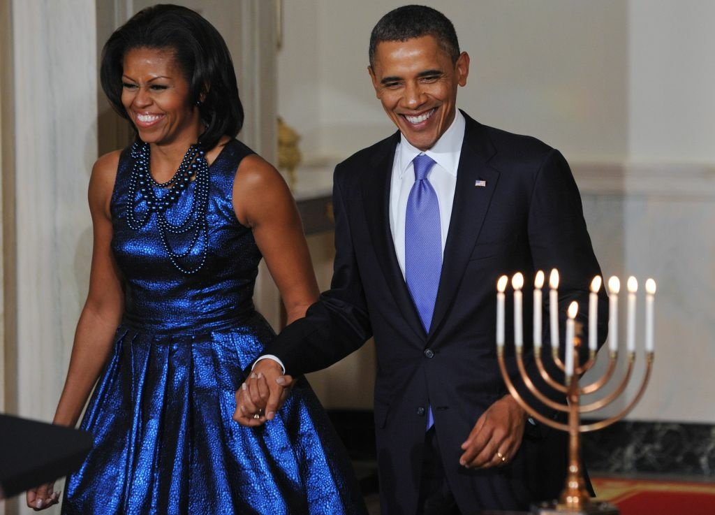 US President Barack Obama and First Lady Michelle Obama arrive for a Hanukkah reception on December 8, 2011 in the Grand Foyer of the White House in Washington.