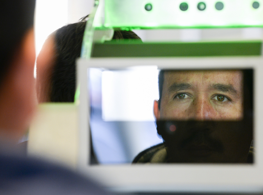 A pedestrian crossing from Mexico into the United States at the Otay Mesa Port of Entry has his facial features and eyes scanned at a biometric kiosk Thursday, Dec. 10, 2015, in San Diego.  On Thursday, U.S. Customs and Border Protection began capturing facial and eye scans of foreigners entering the country at San Diego's Otay Mesa port of entry on foot.