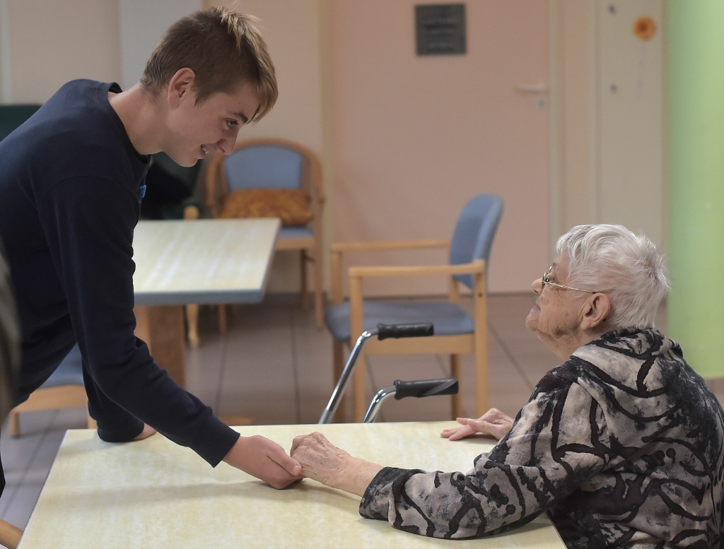 A teenager holds the hand of a woman with Alzheimer's disease in a retirement home on October 18, 2016 in Saint Quirin, France.