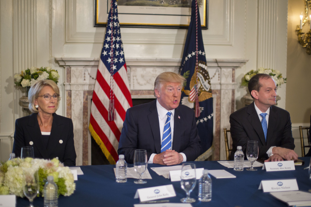 President Trump, flanked by Education Secretary Betsy DeVos and Labor Secretary Alexander Acosta, answers questions in August 2017 at Trump National Golf Club in Bedminster, N.J. Thursday, the White House announced plans to merge the two departments.