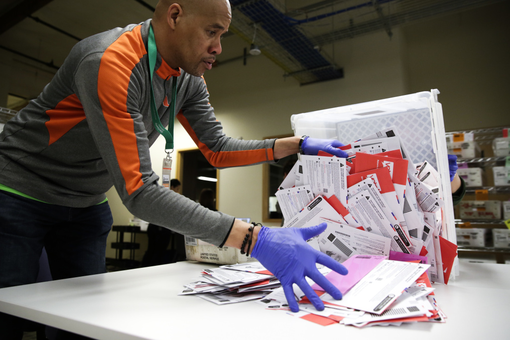 An election worker in Renton, Washington begins processing mail-in ballots during that state's presidential primary in March. Varying state-by-state requirements around signatures and other rules have become the focus of legal fights as absentee voting expands due to the pandemic.