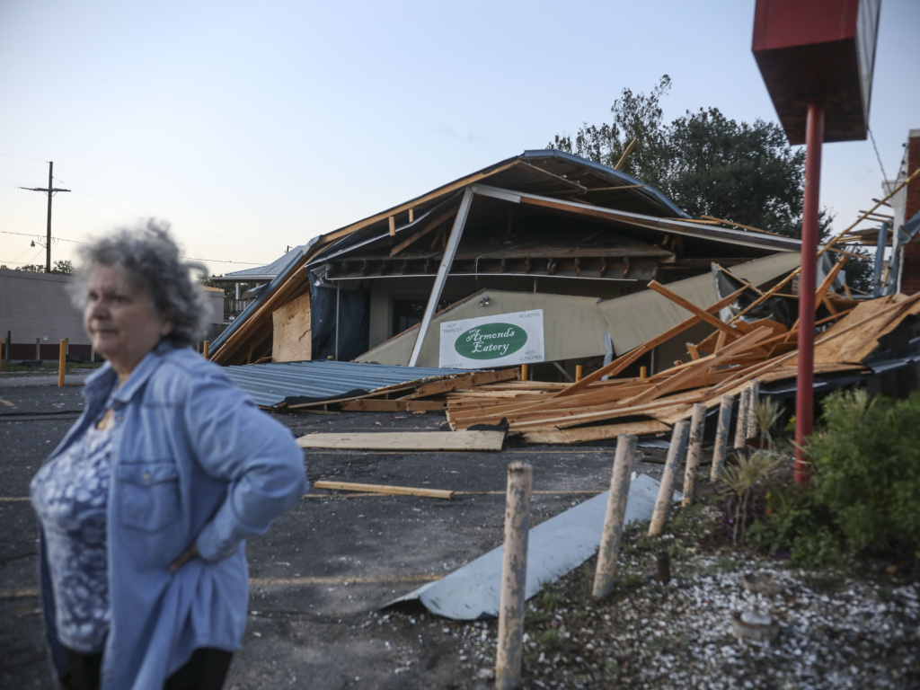 A woman stands in front of a destroyed restaurant after Hurricane Zeta on Oct. 29, 2020, in Chalmette, La. In a postseason analysis, NOAA upgraded Zeta's windspeeds, saying it was a