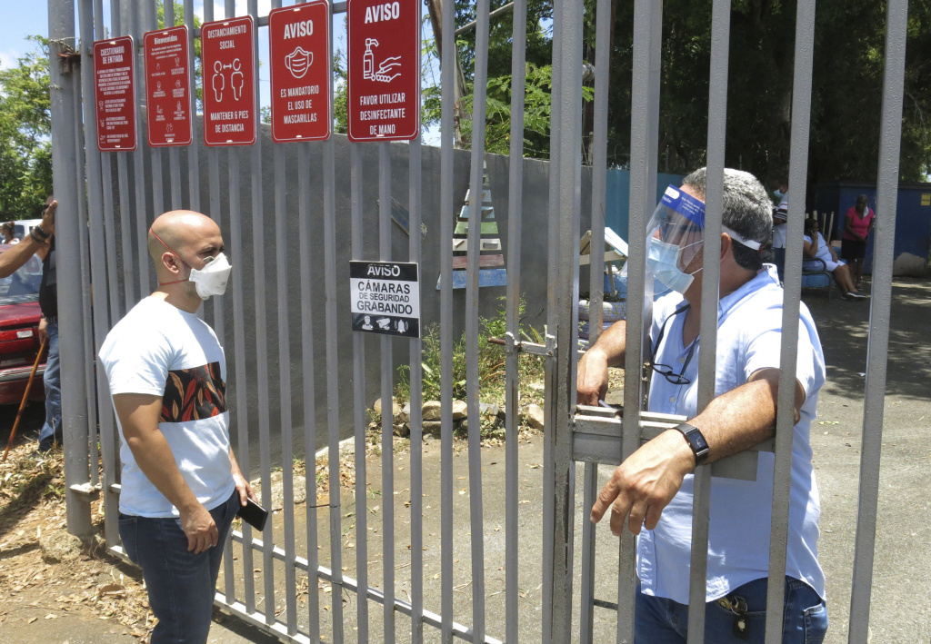 An electoral official (right) tells a voter that ballots haven't arrived at a voting center Sunday in Carolina, Puerto Rico.