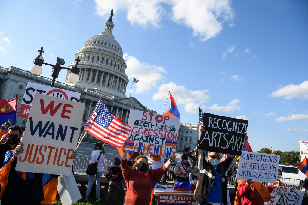 Armenian-Americans hold signs and flags as they protest against the conflict between Azerbaijan and the Armenian enclave of Nagorno-Karabakh and Turkey's support for Azerbaijan in front of the US Capitol in Washington, DC.