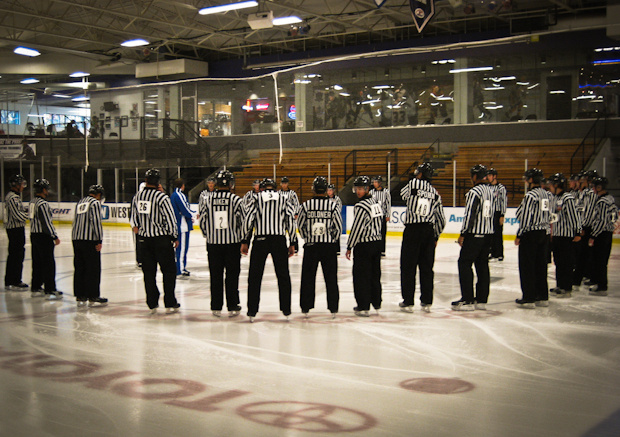 National Hockey League referees gather students in a huddle to teach them how to be better hockey officials.