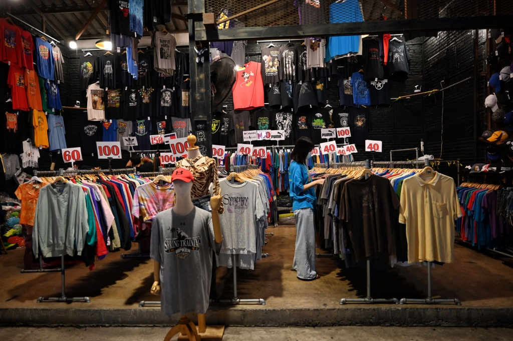 This photo taken on April 16, 2021 shows a lone customer at a T-shirt thrift shop at the Train Night Market Ratchada in Bangkok, Thailand.