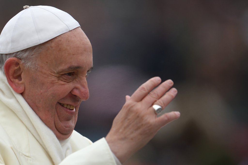 Pope Francis greets the crowd as he arrives for his general audience at St Peter's square on November 27, 2013 at the Vatican.