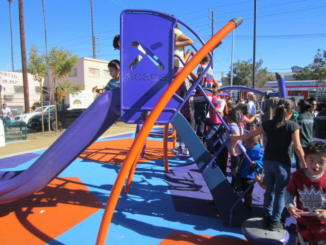 Children line up to go down the slide at the Avalon and Gage Park's grand opening, Jan. 24, 2015.