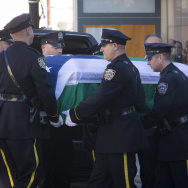 New York City police officers carry the casket of NYPD  officer Rafael Ramos at his wake at Christ Tabernacle Church, in the Glendale section of Queens, on Friday.