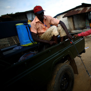 Surveillance team member Osman Sow washes his boots after working in a potentially contaminated area of Freetown, Sierra Leone. Survey teams are sent out every day to assess sick people and dispatch burial teams to collect the dead.