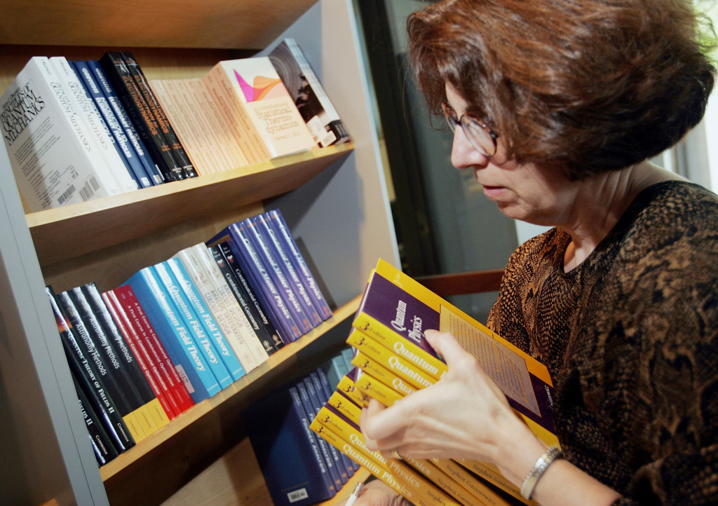 June Kapitan, owner of Quantumbooks, stocks a shelf with textbooks.The Government Accountability Office finds that the average student spends almost $900 on textbooks and supplies.
