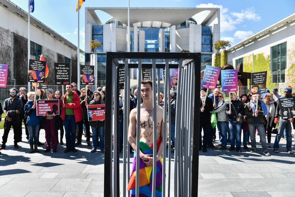 An activist stands naked, wrapped in a rainbow flag, in a mock cage in Berlin during a demonstration calling on Russia to put an end to the persecution of gay men in Chechnya.