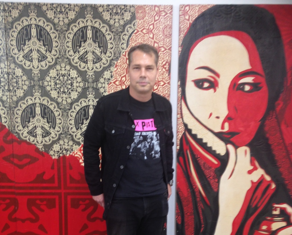 Shepard Fairey with one of his paintings that will be on display in the Beyond the Streets exhibit