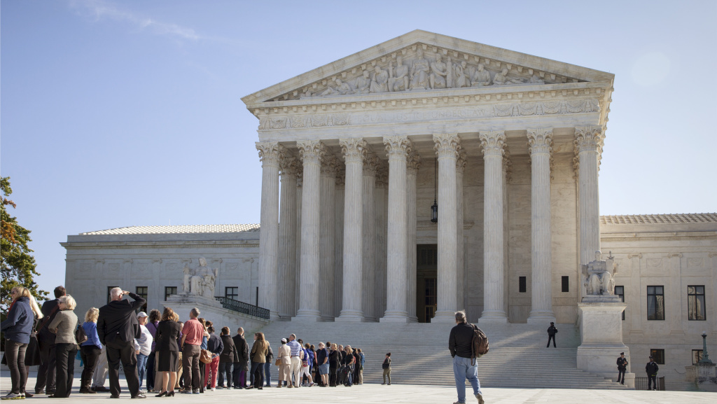 People wait to enter the Supreme Court in Washington Monday as it begins its new term. The justices cleared the way Monday for an immediate expansion of same-sex marriage by unexpectedly and tersely turning away appeals from five states seeking to prohibit gay and lesbian unions.
