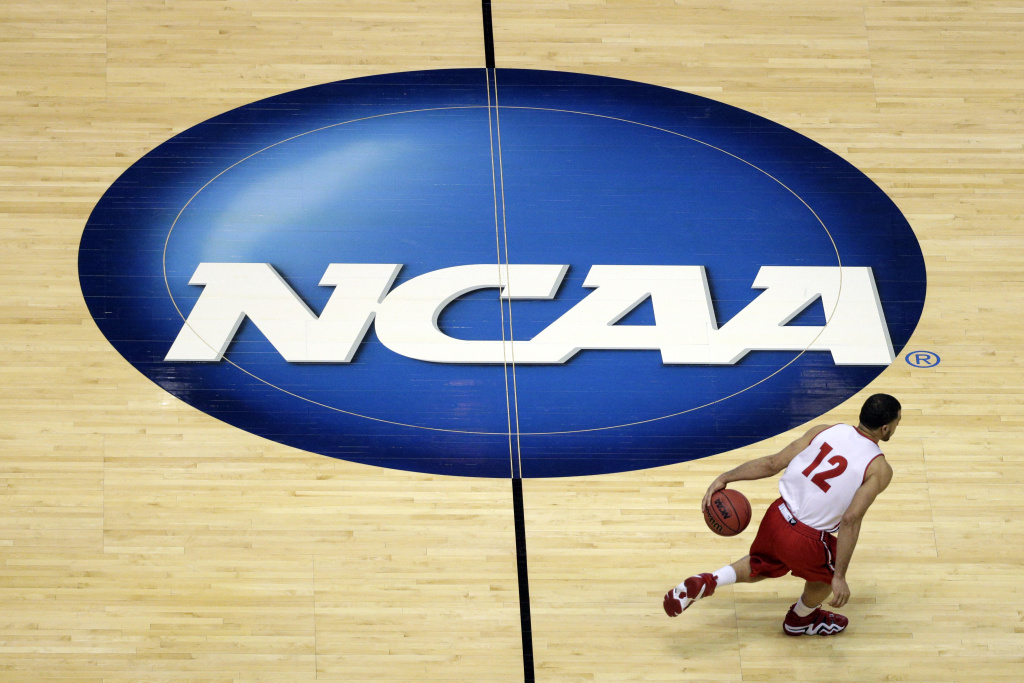 In this March 26, 2014, file photo, Wisconsin's Traevon Jackson dribbles past the NCAA logo during practice at the NCAA men's college basketball tournament in Anaheim, Calif. Anaheim was selected to host regional games for the 2016 tournament, the NCAA said Monday.