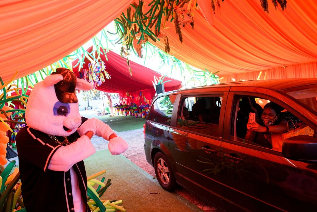 People watch as they drive through Easter themed tents after receiving kits to host their own Covid-19 pandemic safe celebrations during a drive-in Easter Eggstravaganza for children including foster youth during an event held by Guardians of Love and Los Angeles Mission on April 2, 2021 in Los Angeles, California.