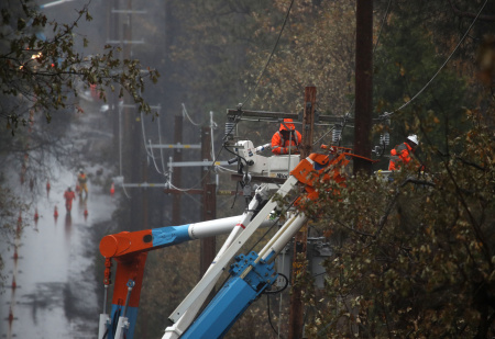 Pacific Gas and Electric (PG&E) crews repair power lines that were destroyed by the Camp Fire on November 21, 2018 in Paradise, California