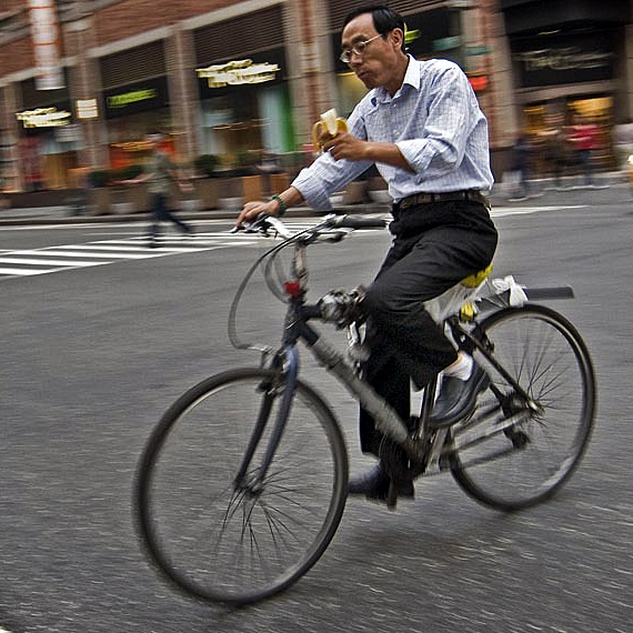 A man eats a banana while biking in New York.