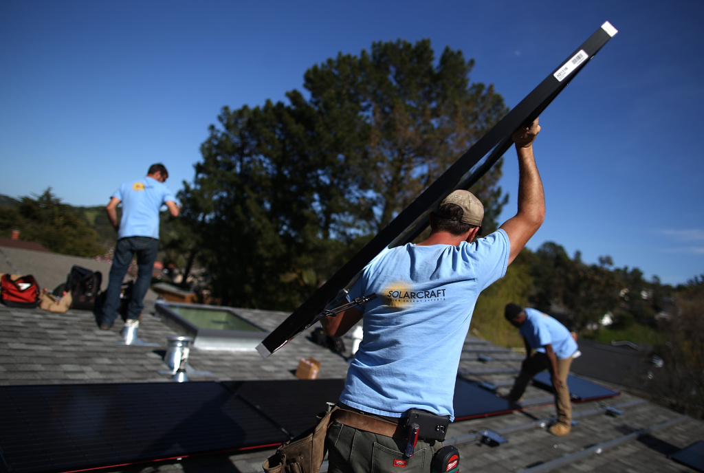 SolarCraft worker Joel Overly carries a solar panel on the roof of a home on February 26, 2015 in San Rafael, California.