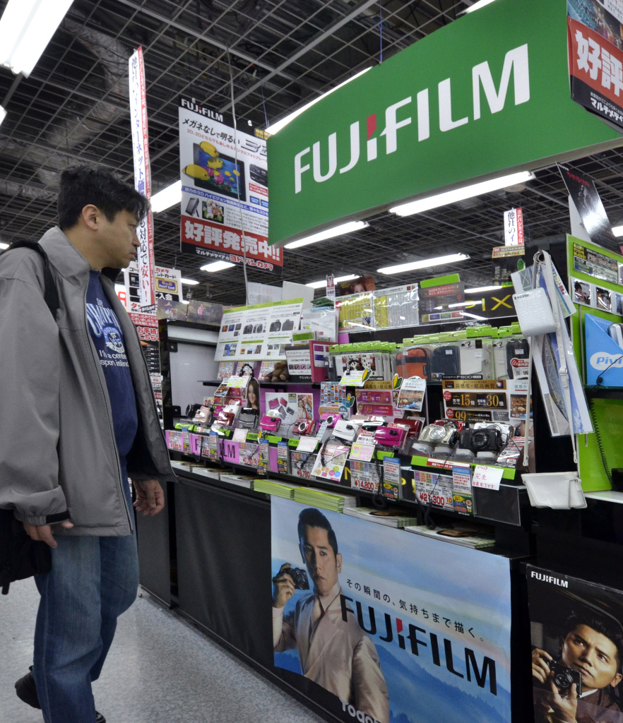 A customer inspects Fujifilm digital cameras at a Tokyo camera shop on January 30, 2012.  Fujifilm has offered scandal-hit Olympus a capital and business tie-up, as it announced a slump in third-quarter profits. Olympus is reportedly seeking a corporate alliance to shore up its finances after admitting covering up 1.7 billion USD in losses, and several Japanese and foreign firms including Sony have been mentioned as possible partners.