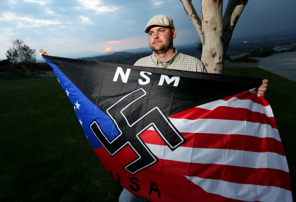 Jeff Hall holds a Neo Nazi flag while standing at Sycamore Highlands Park near his home in Riverside, Calif., on Friday, Oct. 22, 2010. Hall was shot to death on May 1, 2011 by his 10-yar-old son. Photo credit: Sandy Huffaker/AP
