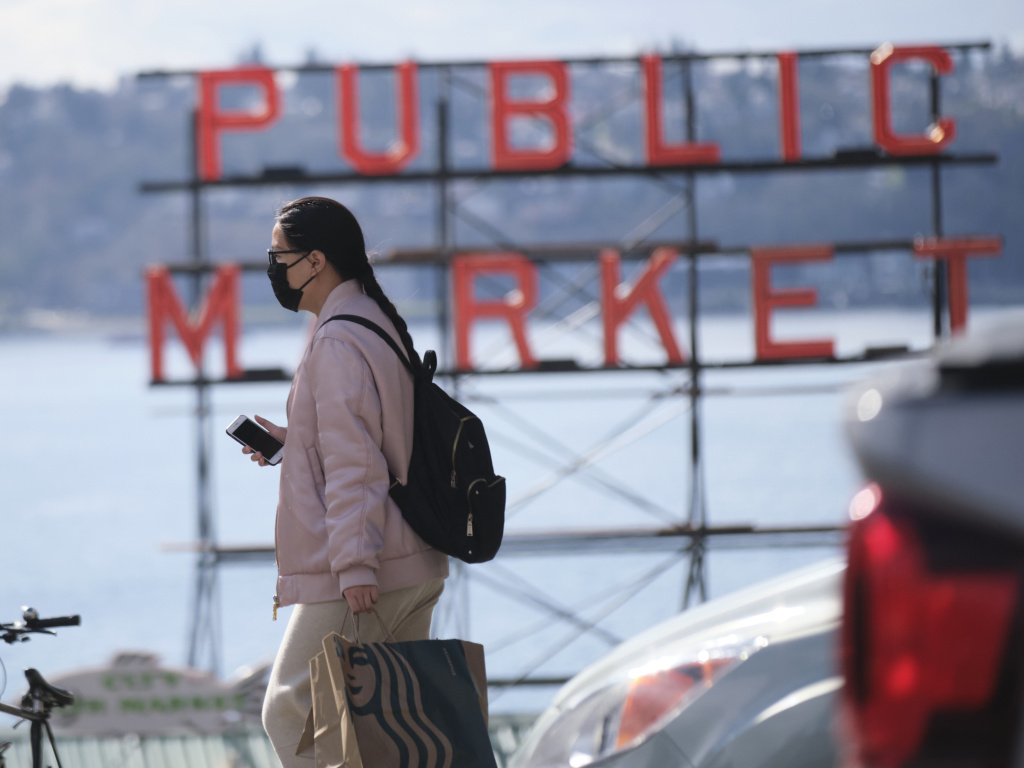 A passerby near the the Pike Place Public Market in Seattle on Wednesday. Washington is one of the states closing schools and other public gathering places to help fight the coronavirus.