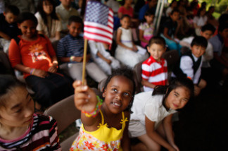 Six-year-old Rahel Williams holds up a United States flag during a ceremony where she and 24 other children became U.S. citizens at the Sully Historic Site in Chantilly, Virginia in May.  (Photo by Chip Somodevilla/Getty Images)