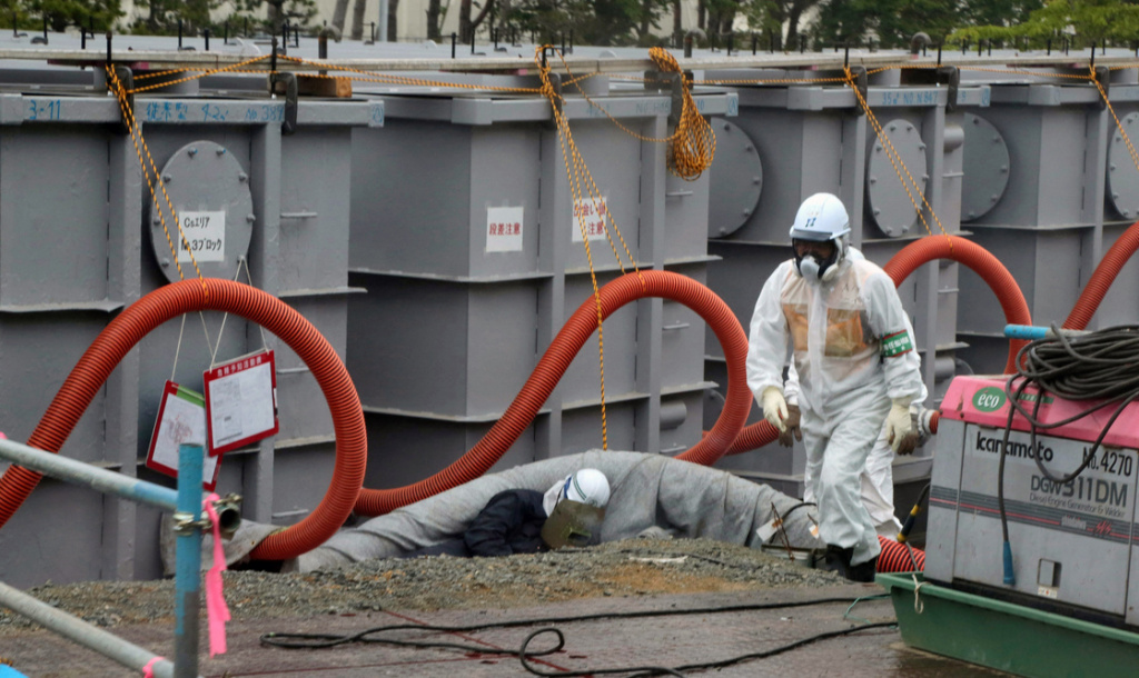 In this file photo, Tokyo Electric Power Co (TEPCO) workers work on waste water tanks at Japan's Fukushima Daiichi nuclear plant in the town of Okuma, Fukushima prefecture in Japan on June 12, 2013. Officials say an earthquake has struck the region for the second time in two years.