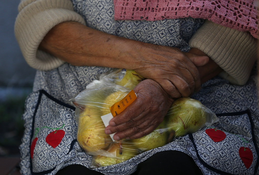 A woman holds a bag of pears as she waits in line to receive free food at the Richmond Emergency Food Bank on November 1, 2013 in Richmond, California.
