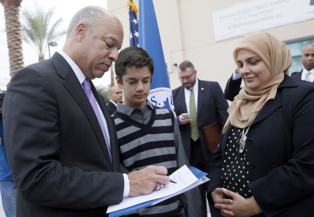 Homeland Security Secretary Jeh Johnson, left, gives an autograph to Hamza Salem, 14, as his mother Metra Salem watches following a news conference after the secretary's visit to the Islamic Center of the San Gabriel Valley in Rowland Heights, Calif., Thursday, Nov. 13, 2014. (AP Photo/Nick Ut)