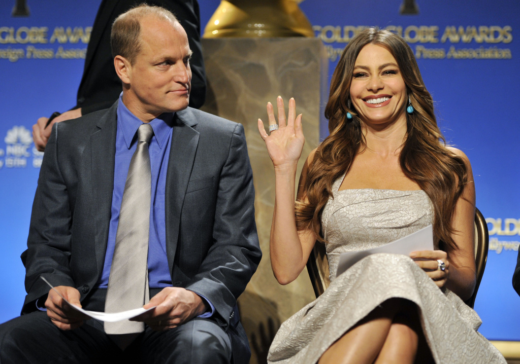 Presenter Sofia Vergara waves to photographers alongside fellow presenter Woody Harrelson before they announced nominations for the 69th Annual Golden Globe Awards.