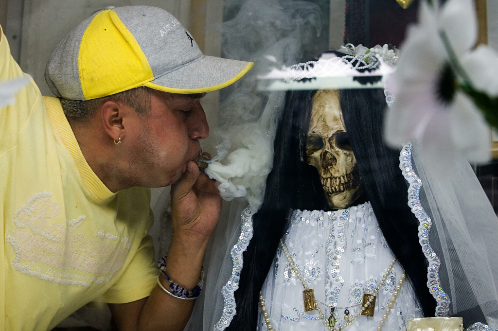 A devotee of the 'Santa Muerte' (Holy Death), throws smoke at a figure of the goddess at the shrine in her honour in the popular Tepito shantytown, in Mexico City, November 1, 2007, coinciding with the Day of the Dead celebrations. The cult of this pseudo-religious skeletal image, also known as 'La Santísima', 'Doña Sebastiana', 'Little White Girl' or 'The Skinny Girl', is thought to date back to pre-Columbian times. Every first day of each month, thousands of Mexican devotees, attend the different shirnes to make offerings and ask for petitions. The Holy Death currently has some two million faithfuls in Mexico.  AFP PHOTO/Luis ACOSTA (Photo credit should read LUIS ACOSTA/AFP/Getty Images)