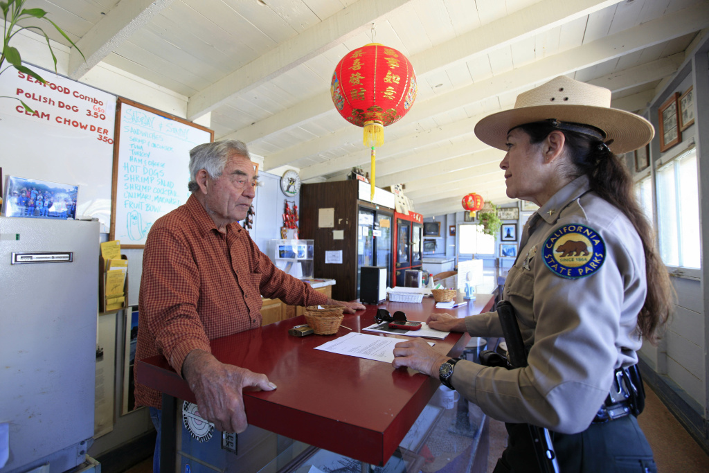 In this photo taken Friday July 15, 2011, park resident Frank Quan, left, talks with Danita Rodriguez, right, a superintendent with California State Parks in the store that Quan runs at China Camp State Park, Calif. This former 19th Century Chinese shrimping village on the northern shores of San Francisco Bay is one of 70 state parks slated for closure.